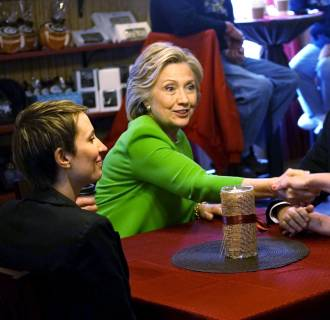 Image: Former U.S. Secretary of State Clinton talks with local residents as she campaigns at the Jones Street Java House in LeClaire, Iowa