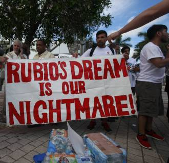 Image: Protestors against U.S. Senator Rubio's immigration policies gather outside the Freedom Tower prior to Rubio