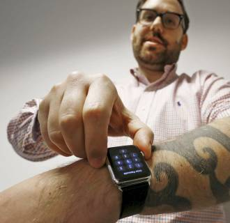 Image: Reuters journalist Matt Siegel inputs his passcode onto his Apple Watch as his tattoos prevent the device's sensors from correctly detecting his skin, in Sydney