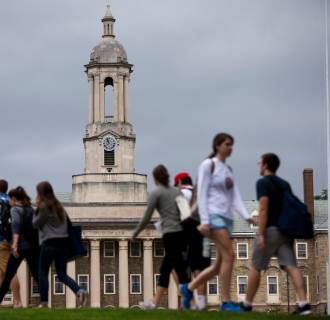 Image: Students walk past the Old Main building on the Penn State campus