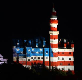 Image: The castle Neuschwanstein, near Fuessen, southern Germany, is illuminated with the US flag.