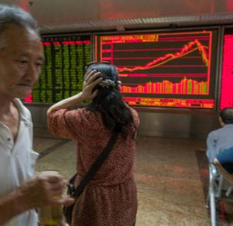 Image: Woman holds her head while watching stock price movements