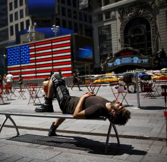 Image: A man takes a nap during a sunny day at Times Square in New York