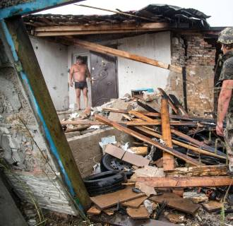 Image: A Ukrainian serviceman examine a destroyed house after shelling between Ukrainian forces and pro-Russian seperatists