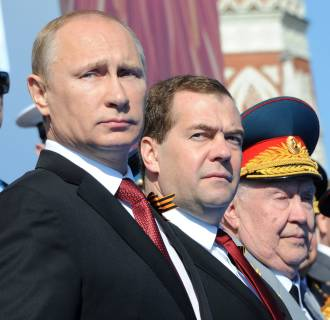 Image: Russia's President Vladimir Putin (L) and Prime Minister Dmitry Medvedev (2nd L) attend a Victory Day parade at the Red Square in Moscow, on May  9, 2014.