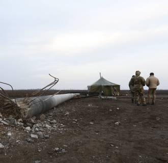 Image: Security personnel, wearing a camouflage uniform, stand guard near a damaged electrical pylon near the village of Chaplynka in Kherson region, Ukraine
