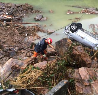 Image: A rescue worker is seen next to an overturned car at the site of a landslide caused by heavy rains brought by Typhoon Megi, in Sucun Village, Lishui