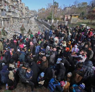 Image: Syrian residents fleeing the violence gather at a checkpoint