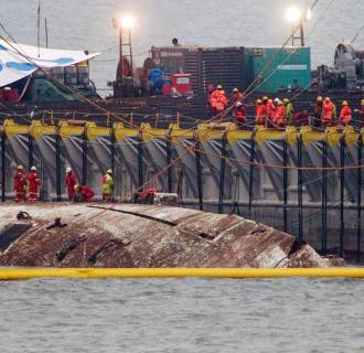 Image: The sunken ferry Sewol is raised during its salvage operations at the sea off Jindo