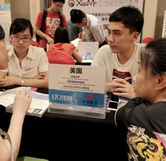 Image: Education consultants talk with visitors about studying in the United States during an education expo in Wuhan, central Chinas Hubei province, July 6, 2013.