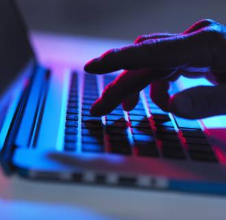 Image: Silhouette of male hand typing on laptop keyboard at night