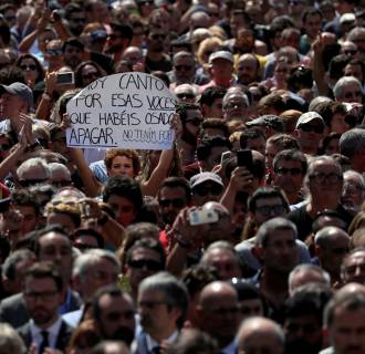 Image: A woman holds a sign that reads