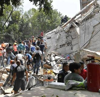 Image: People remove debris of a collapsed building after a quake rattled Mexico City