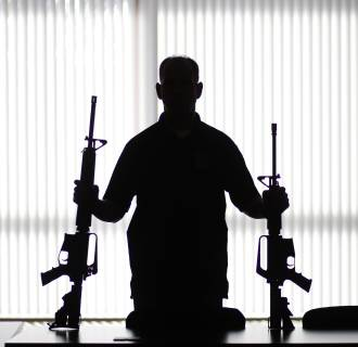 Image: An ATF agent poses with homemade rifles, or