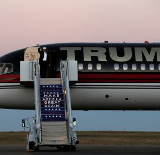 Image: Trump waves as he walks off his plane at a campaign rally in Colorado Springs