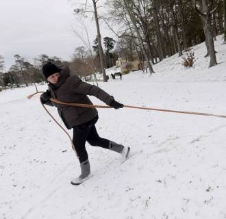 Image: Emily Massey pulls her daughter down a snowy hill in Shreveport, La.