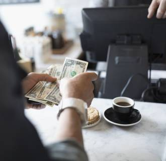 Image: Customer paying with cash at cafe counter