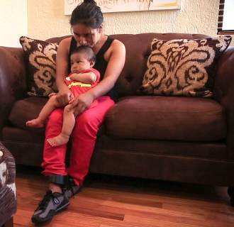 Image: Micaela cradles her 6-month-old infant while wearing a GPS ankle monitor.