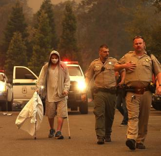 Image: Hospital workers and first responders evacuate patients from the Feather River Hospital as the Camp Fire moves through the area
