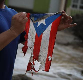 Image: Jose Javier Santana holds a Puerto Rican flag he found after Hurricane Maria passed through Utuado on Oct. 6, 2017.