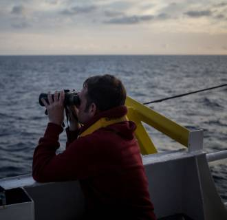 Image: One of the crew members of rescue vessel Sea Watch 3 scans the sea with binoculars