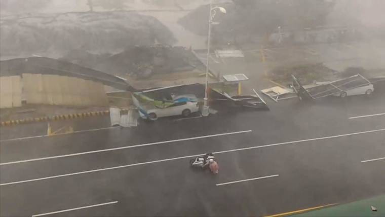 Typhoon's Strong Winds Knock Over Driver